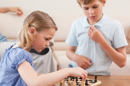Children playing chess in a living room photo