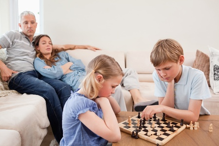 Siblings playing chess in front of their parents in a living room Stock Photo - 11683824