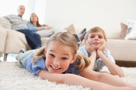 Siblings lying on a carpet while their parents are sitting on a sofa photo