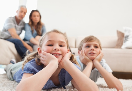 Children lying on a carpet while their parents are sitting on a sofa photo