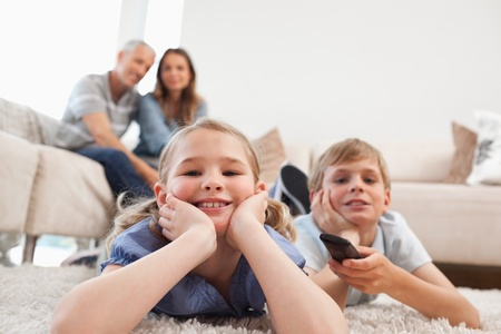 Siblings watching television with their parents on the background in a living room photo