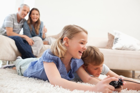 Siblings playing video games with their parents on the background in a living room photo
