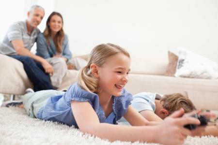 niños jugando videojuegos: Los niños que juegan videojuegos con sus padres en el fondo de una sala de estar