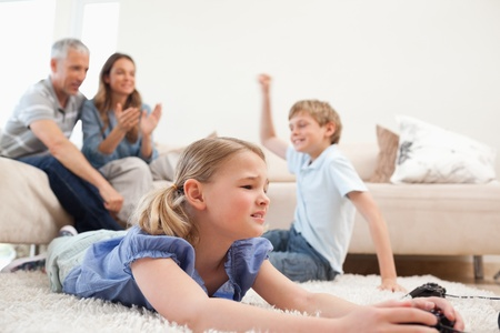 Cute children playing video games with their parents on the background in the living room photo