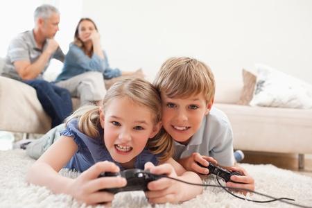 niños jugando videojuegos: Los niños alegres jugando videojuegos con sus padres en el fondo de una sala de estar