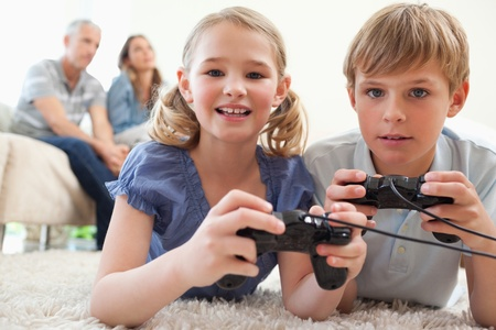 Playful siblings playing video games with their parents on the background in a living room photo