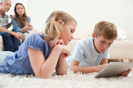 Siblings using a tablet computer with their parents on the background in a living room photo