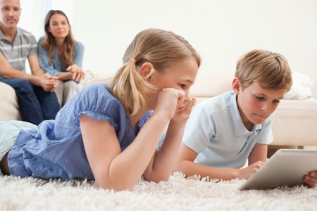 Children using a tablet computer with their parents on the background in a living room photo