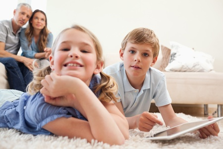 Happy children using a tablet computer with their parents on the background in a living room photo