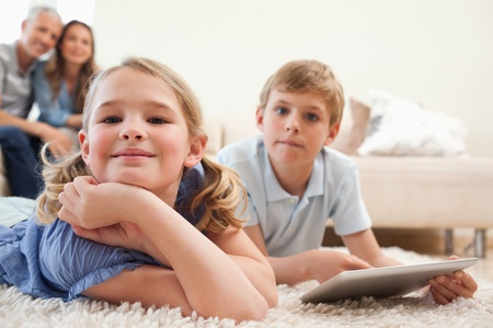 Happy siblings using a tablet computer with their parents on the background in a living room  photo