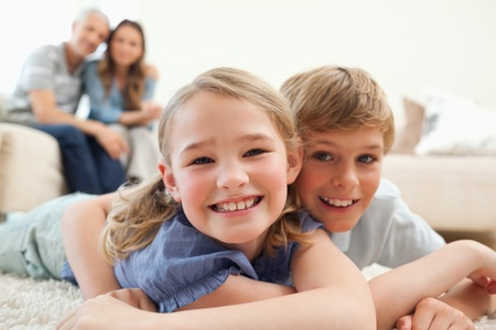 Happy siblings posing on a carpet with their parents on the background in a living room photo