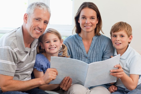 Happy family reading a book together in a living room Stock Photo - 11682878