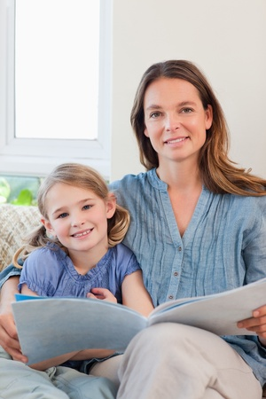 Portrait of a mother reading a book to her daughter in a living room photo