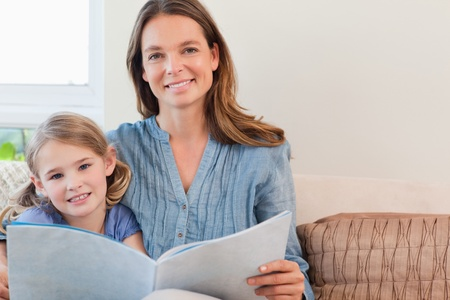 Happy mother reading a book to her daughter in a living room photo