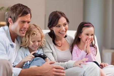 familia jugando: Familia feliz jugando juegos de video juntos en una sala de estar