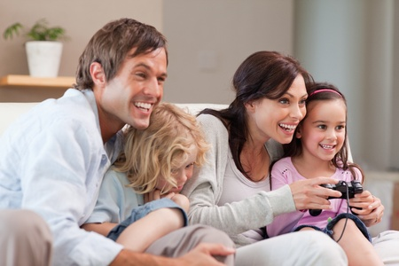Delighted family playing video games together in a living room photo