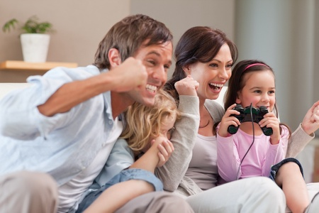 Positive family playing video games together in a living room photo
