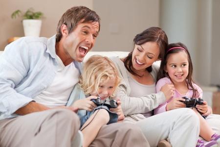 jugando videojuegos: Re�rse de la familia jugando a videojuegos en una sala de estar