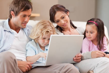 Calm family using a laptop in a living room photo