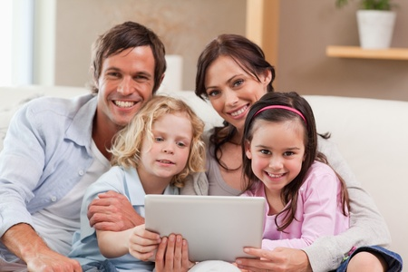 Charming family using a tablet computer in a living room photo