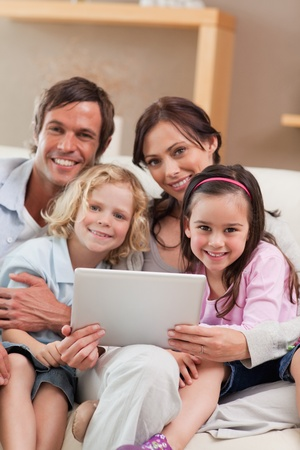 Portrait of a family using a tablet computer in a living room photo