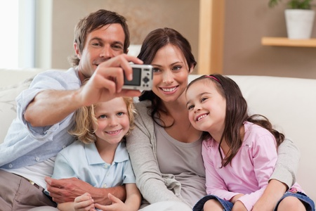 Father taking a picture of his family in the living room photo