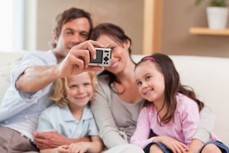 Happy father taking a picture of his family in a living room photo