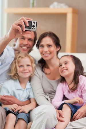 Portrait of a father taking a picture of his family in a living room photo