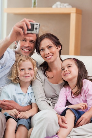 Portrait of a happy father taking a picture of his family in a living room