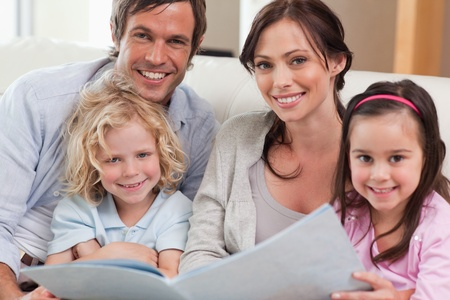 Close up of a family looking at a photo album in a living room Stock Photo - 11681574