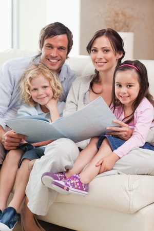 Portrait of a family looking at a photo album in a living room Stock Photo - 11683700