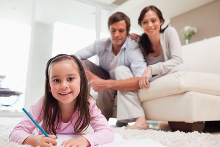 Girl drawing with her parents in the background while lying on a carpet photo