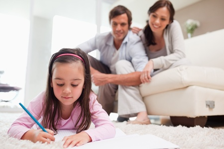 Little girl drawing with her parents in the background while lying on a carpet photo