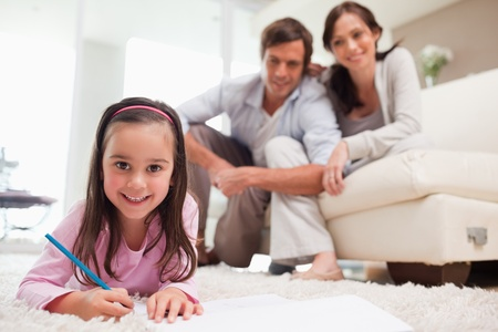 Cute girl drawing with her parents in the background in a living room photo