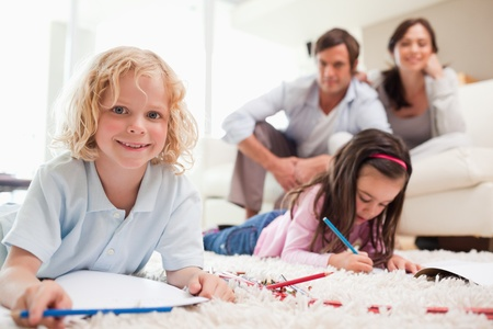 living room boy: Children drawing while their parents are in the background in a living room