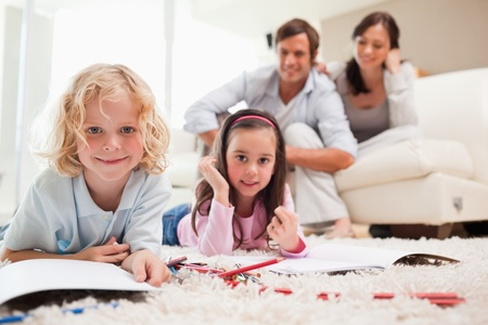 Cute siblings drawing while their parents are in the background in a living room photo