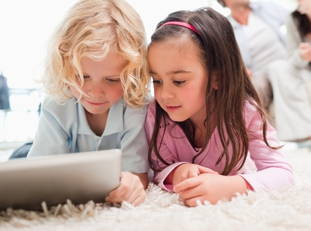 Children using a tablet computer while their parents are in the background in a living room photo