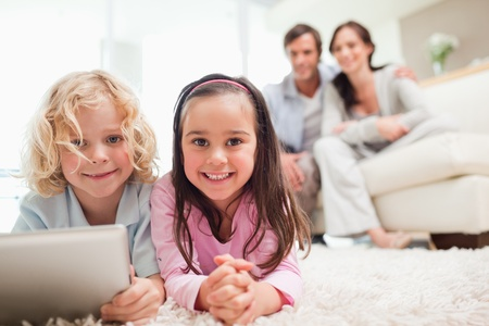 Siblings using a tablet computer while their parents are in the background in a living room photo