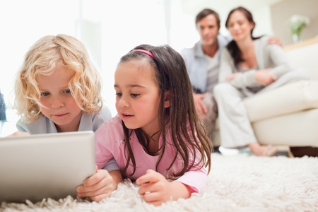 Cute siblings using a tablet computer while their parents are in the background in a living room photo