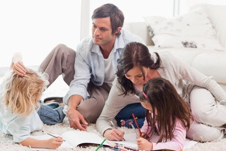 Family drawing together in a living room photo
