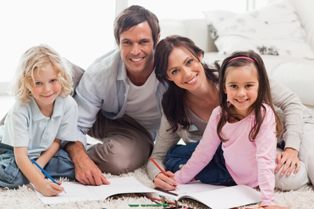 Charming family drawing together in a living room photo