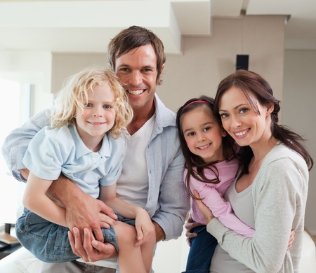 Charming family posing together in a living room photo