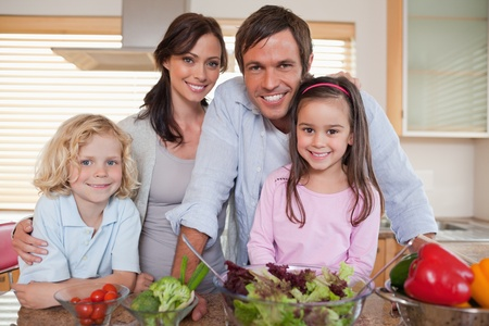 Family preparing a salad in a kitchen photo