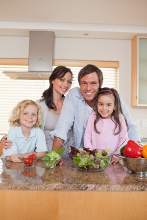 Portrait of a family preparing a salad in a kitchen photo