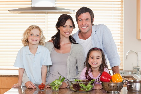 Family preparing a salad together in a kitchen Stock Photo - 11683644