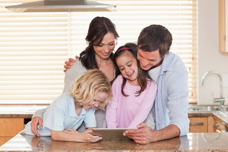 Family using a tablet computer together in a kitchen photo