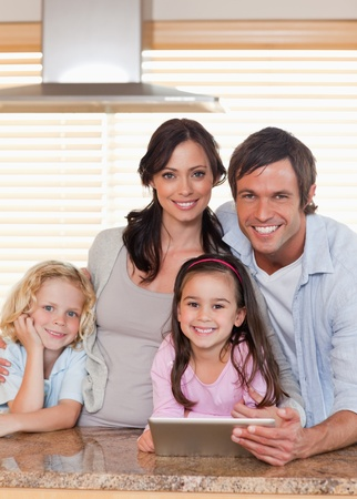Portrait of a smiling family using a tablet computer together in a kitchen photo