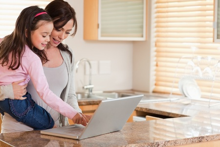 Girl and her mother using a laptop in a kitchen photo