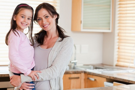 Girl and her mother posing in a kitchen photo