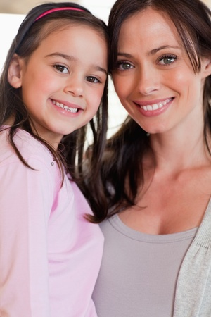 Portrait of a girl and her mother posing while smiling at the camera photo